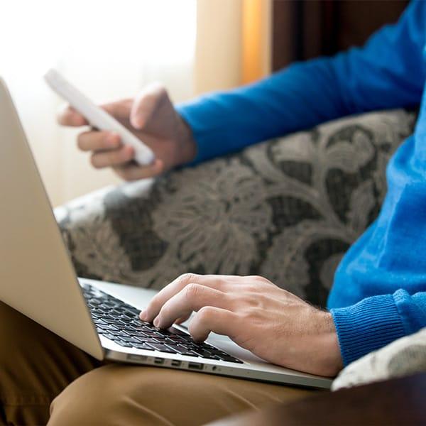 Männerhand mit Laptop und Telefon